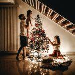 Una familia decorando un arbol de Navidad