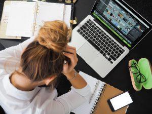Una chica frente del computador y na problema con reembolso del préstamo
