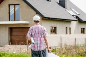 Nueva casa durante la construcción - un architecto con proyecciones a mano